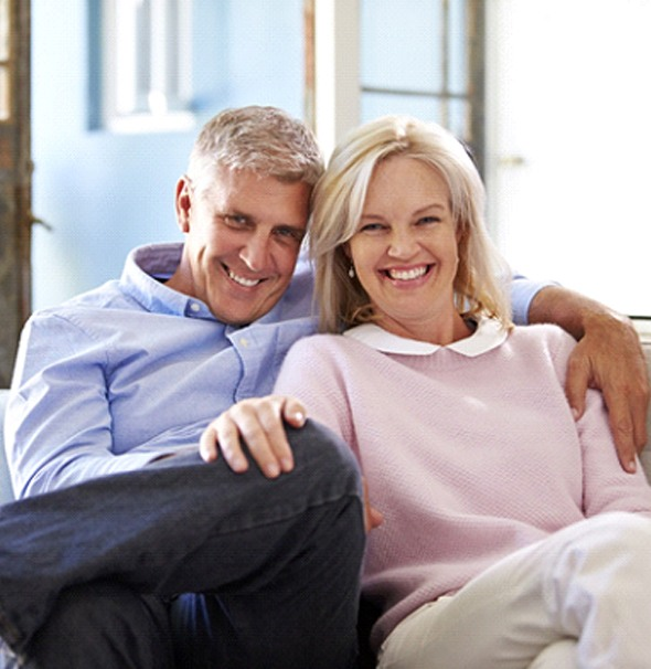 older couple sitting in couch and smiling with All-on-4 in Braintree