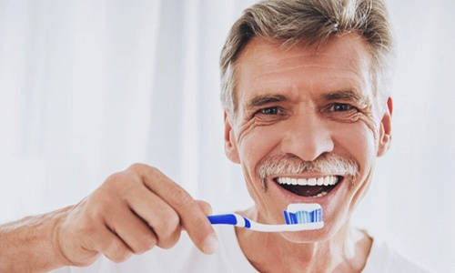 older man in white shirt brushing his teeth
