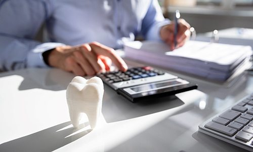 A man sitting at a desk with a calculator and a model of a tooth