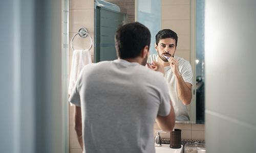 A young man standing in front of the mirror brushing his teeth