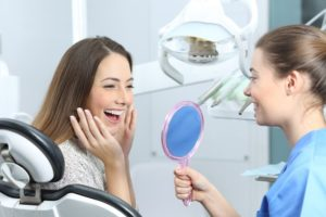 Woman appreciating her smile after visiting her Braintree dentist