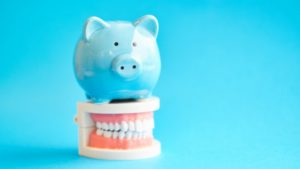 Blue piggy bank atop model jaw with dental implants in Braintree