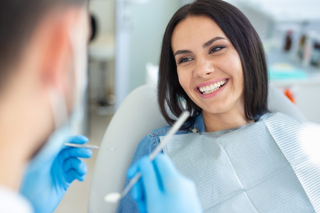 Patient smiling during checkup with cosmetic dentist