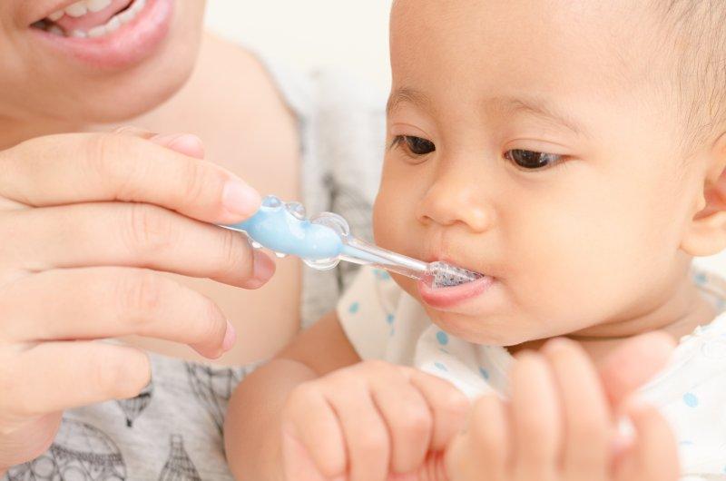 Closeup of mom brushing baby's teeth