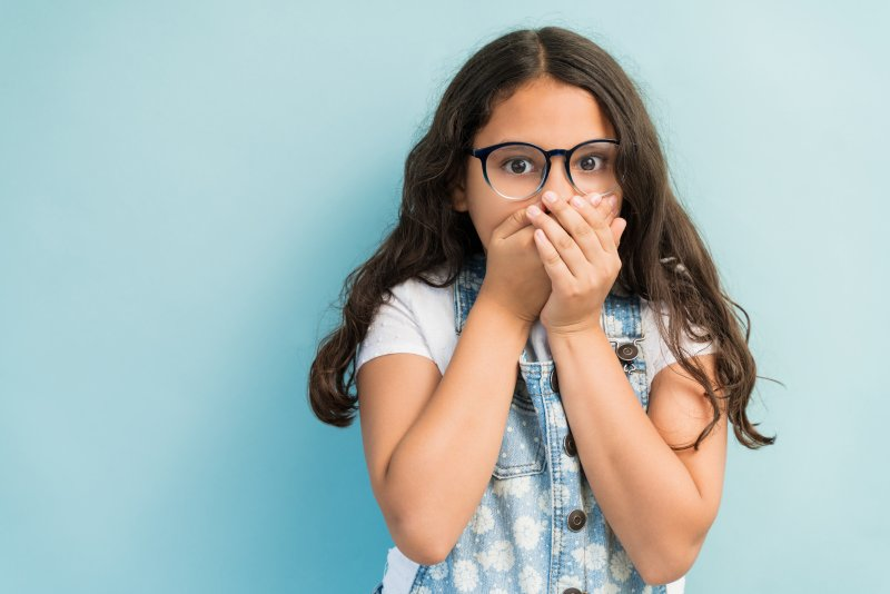 Young girl covering her mouth in shock